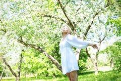 Szczęśliwa blondynki kobieta na tle kwitnący wiosna ogród z ona ręki podnosić niebo obrazy royalty free