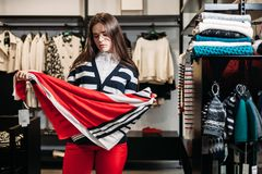 Szczęśliwa dziewczyna wybiera szalika i pozuje w centrum handlowym lub sklepie odzieżowym zdjęcia royalty free