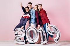 Szczęśliwa firma dwa dziewczyny i dwa faceta ubierającego w eleganckich ubraniach trzymamy balony w formie liczb 2019 dalej zdjęcie stock
