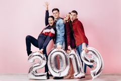 Szczęśliwa firma dwa dziewczyny i dwa faceta ubierającego w eleganckich ubraniach trzymamy balony w formie liczb 2019 dalej zdjęcia royalty free