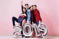 Szczęśliwa firma dwa dziewczyny i dwa faceta ubierającego w eleganckich ubraniach trzymamy balony w formie liczb 2019 dalej zdjęcie royalty free