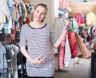 Szczęśliwa kobieta w ciąży z torbami na zakupy w odzież sklepie na zakupy zdjęcie royalty free