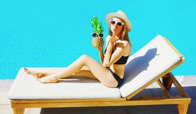 Szczęśliwa kobieta wysyła cukierki powietrza buziaka z ananasowym obsiadaniem na deckchair nad błękitne wody basenu tłem obrazy stock