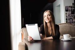 Szczęśliwa młoda kobieta pije kawę i używa pastylka komputer w sklepie z kawą, herbaciany zdjęcie royalty free