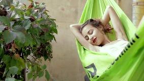 Szczęśliwa młoda kobieta relaksująca kłama w hamaku na balkonowym domu Kobieta wygrzewa się i sunbathes w hamaku zdjęcie wideo