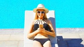 szczęśliwa młoda kobieta używa smartphone lying on the beach na deckchair nad błękitne wody basenu tłem obraz royalty free