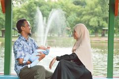 Szczęśliwa młoda muzułmańska rodzina z dzieckiem cieszy się dzień przy plenerową parkową pobliską wodną fontanną podczas dnia cza zdjęcie royalty free