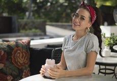 Szczęśliwa młoda uśmiechnięta brunetki kobieta pozuje przy stołem w plenerowej restauracji obrazy stock