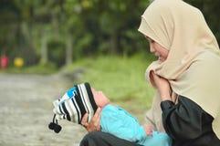 Szczęśliwa muzułmańska hijab matka trzyma pięknego dziecka podczas gdy jej todler płacz w plenerowym terenie zdjęcie stock