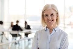 Szczęśliwa pomyślna starzejąca się biznesowa dama pozuje patrzejący kamerę fotografia stock