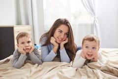 Szczęśliwa potomstwo matka ubierająca w bławej piżamie kłaść z jej dwa małymi synami trzyma ich ręki pod ich podbródkami dalej zdjęcia stock