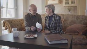 Szczęśliwa starsza para siedzi w domu opowiadać z each inny Związki rodzinni swobodny ruch zbiory