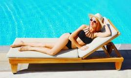 szczęśliwa szczupła kobieta kłama na deckchair nad błękitne wody basenu tłem zdjęcia stock