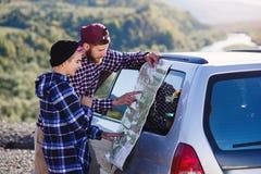 Szczęśliwa turystyczna para z papierową mapą blisko samochodu Uśmiechnięci młodzi ludzie używa mapę Podróżować dzierżawiącym samo zdjęcie stock