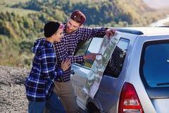 Szczęśliwa turystyczna para z papierową mapą blisko samochodu Uśmiechnięci młodzi ludzie używa mapę Podróżować dzierżawiącym samo fotografia royalty free