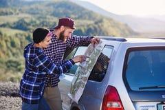 Szczęśliwa turystyczna para z papierową mapą blisko samochodu Uśmiechnięci młodzi ludzie używa mapę Podróżować dzierżawiącym samo obrazy royalty free