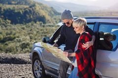 Szczęśliwa turystyczna para z papierowej mapy pobliskim dzierżawiącym samochodem Modni młodzi ludzie używa mapę Podróżować samoch fotografia stock