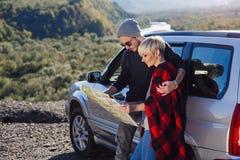 Szczęśliwa turystyczna para z papierowej mapy pobliskim dzierżawiącym samochodem Modni młodzi ludzie używa mapę Podróżować samoch obrazy stock