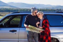 Szczęśliwa turystyczna para z papierowej mapy pobliskim dzierżawiącym samochodem Modni młodzi ludzie używa mapę Podróżować samoch zdjęcia royalty free