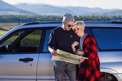 Szczęśliwa turystyczna para z papierowej mapy pobliskim dzierżawiącym samochodem Modni młodzi ludzie używa mapę Podróżować samoch zdjęcie stock