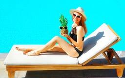 szczęśliwa uśmiechnięta kobieta kłama na deckchair z ananasem nad błękitne wody basenu tłem zdjęcia royalty free