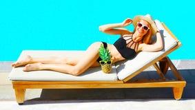 Szczęśliwa uśmiechnięta kobieta z ananasem kłama na deckchair nad błękitne wody basenu tłem zdjęcia royalty free