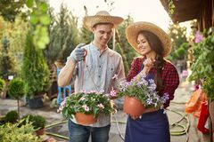 Szczęśliwe faceta i dziewczyny ogrodniczki w słomianych kapeluszy chwycie puszkują z petunią na ogrodowej ścieżce wewnątrz na sło zdjęcie royalty free