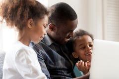 Szczęśliwego amerykanin afrykańskiego pochodzenia zegarka młode rodzinne kreskówki na laptopie obrazy royalty free