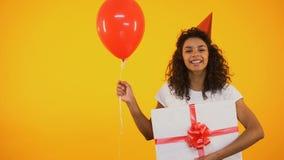 Szczęśliwego nastolatka mienia balonowy i ogromny giftbox, odświętność urodziny, powitania zbiory
