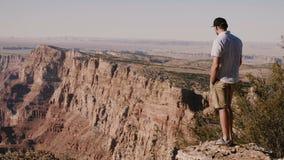 Szczęśliwego pomyślnego młodego turystycznego mężczyzny dopatrywania epicka sceneria nad Grand Canyon górami, szeroki filmowy tło zbiory