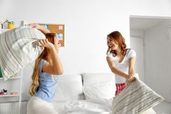 Szczęśliwi nastoletni dziewczyna przyjaciele walczy poduszki w domu obrazy stock