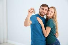 Szczęśliwi potomstwa dobierają się z kluczem od ich nowego domu indoors zdjęcie stock