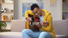 Szczęśliwy afroamerykański nastolatek bawić się gitarę, cieszy się ulubionego hobby, czas wolny zbiory