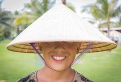Szczęśliwy azjata jest ubranym wietnamczyka kapelusz i ono uśmiecha się z Chińskimi nowy rok powitaniami, żadny oczy jest widoczn zdjęcia royalty free