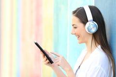 Szczęśliwy dziewczyny dopatrywanie i słuchający wideo na pastylce zdjęcie royalty free