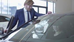 Szczęśliwy mężczyzna i kobieta dyskutuje którego kupować w nowożytnym motorowym przedstawieniu samochód Kobieta daje pastylce męż zdjęcie wideo