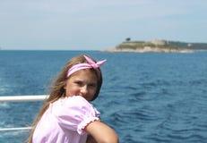 Szczęśliwy małej dziewczynki żeglowanie w łodzi ono uśmiecha się przy morzem na lato rejsie zdjęcia stock