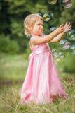 Szczęśliwy małej dziewczynki cyzelatorstwo gulgocze na naturze w parku obraz stock