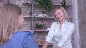 Szczęśliwy macierzyństwo, wesoło uśmiechnięty mum cieszy się komunikuje przy i uścisk z małą córką podczas gdy szczęśliwy wydaje  zdjęcie wideo