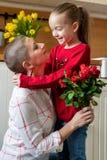 Szczęśliwy matka urodziny lub dnia tło Urocza młoda dziewczyna zaskakuje jej mamy, młody pacjent z nowotworem z bukietem czerwone zdjęcia royalty free