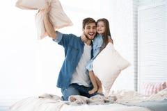 szczęśliwy ojciec i córka bawić się poduszki walkę w łóżku przy rankiem fotografia stock