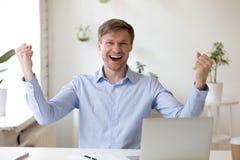 Szczęśliwy pracownik patrzeje kamerę z podnieceniem wielką wiadomością fotografia stock