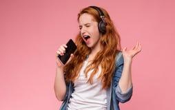 Szczęśliwy rudzielec kobiety śpiew w smartphone lubi mikrofon obrazy stock
