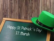 Szczęśliwy St Patricks dnia kredy tekst z zielonym kapeluszem na blackboard i drewniany tło dla kopii przestrzeni obrazy stock
