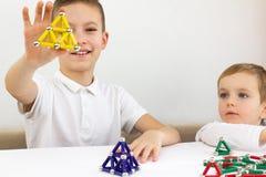 Szczęśliwy uśmiech chłopiec mienia magnes w ręce Rozwój, grzywna motorowe umiejętności i twórczości pojęcie, zdjęcie royalty free