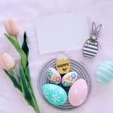 Szczęśliwy Wielkanocny pojęcie z drewnianym królikiem i kolorowymi Easter jajkami na białym futerkowym tle i różowych tulipanach obraz stock