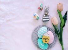 Szczęśliwy Wielkanocny pojęcie z drewnianym królikiem i kolorowymi Easter jajkami na białym futerkowym tle i różowych tulipanach fotografia stock