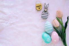 Szczęśliwy Wielkanocny pojęcie z drewnianym królikiem i kolorowymi Easter jajkami na białym futerkowym tle i różowych tulipanach zdjęcia stock