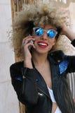 Szczęście dziewczyny kędzierzawy mówienie przy telefonem komórkowym Obrazy Stock