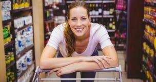 Szczęśliwa ładna brunetka patrzeje kamerę i pcha tramwaj Obrazy Stock
